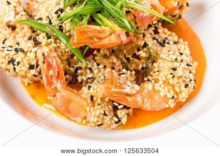 Delicious grilled jumbo shrimps with sesame and sliced scallions on yellow mousse. Macro. Photo can be used as a whole background.