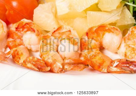 Jumbo shrimp salad with tomatoes and pomelo topped with pine nuts and parmesan cheese. Macro. Photo can be used as a whole background.