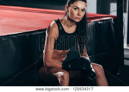brunette woman wearing black sportwear and boxing gloves posing near ring, looking at camera