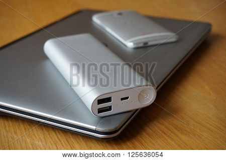 Modern mobile office with metal aluminum devices - cell phone, power bank (external battery) and silver ultrabook (thin portable laptop)