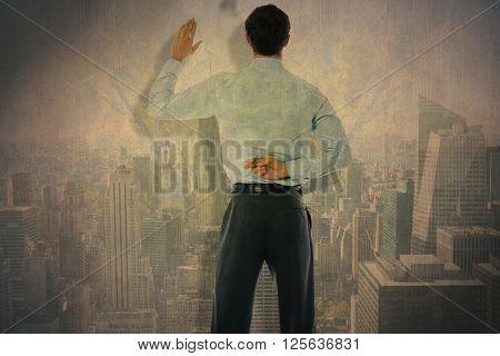 Businessman crossing fingers behind his back against city skyline