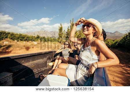 Portrait of happy young friends sitting in a pickup truck going on a road trip. Young people enjoying a country road ride.