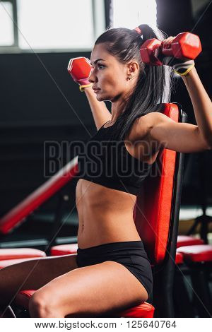 young sporty woman doing exercises with dumbbells in the gym, dumbbell bench press