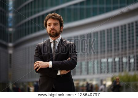 young businessman standing outdoors with arms crossed