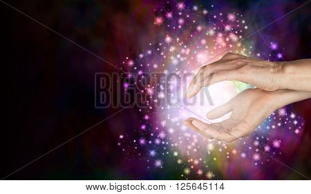 Magi sensing supernatural healing energy -   Female cupped hands with a beautiful sparkling ball of white sparkle filled light around and between  on a deep colored background