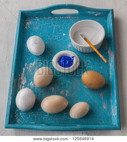 Painting wooden eggs for Easter on blue tray