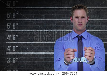 Handsome businessman wearing handcuffs against digital composite image of height measurement