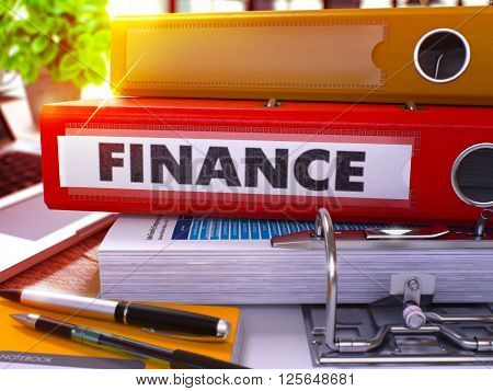 Red Office Folder with Inscription Finance on Office Desktop with Office Supplies and Modern Laptop. Finance Business Concept on Blurred Background. Finance - Toned Image. 3D.