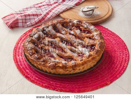 Open cherry pie on the red stand next to a sieve to sprinkle powdered sugar