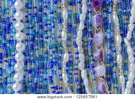 Multicolor beads on naturel wood. Nice blue dark blue and yellow beads on wooden bamboo background