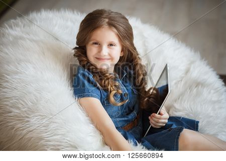 Studio portrait of cute little girl with tablet pc