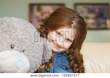 Cute little girl with teddy bear. Stock photo.