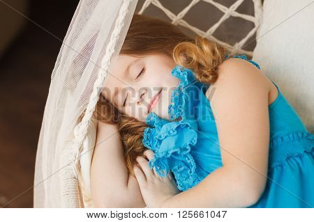 Little girl sleeping in the swings. Stock photo.