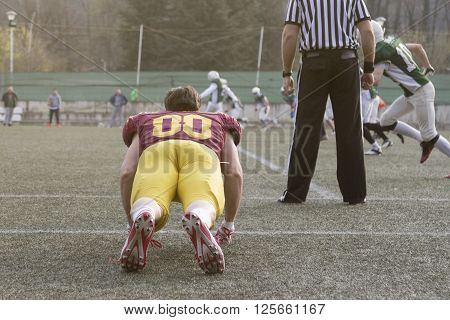 Football player warming up and referee standing next to him on the field