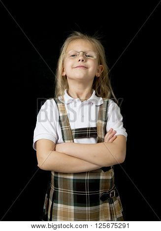 young sweet junior schoolgirl with blonde hair standing happy and smiling isolated in black background wearing school uniform in children education success and fun