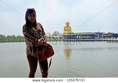 Thai Waman Portrait With Biggest Statue Of Luang Pu Thuat