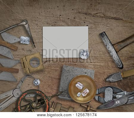 vintage jeweler tools and diamonds on a bench space for text on business card