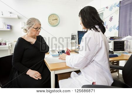 Doctor Explaining Model To Senior Patient Suffering From Shoulde