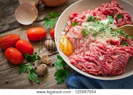 preparing beef steak tartare on bowl with egg