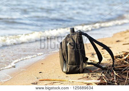 Black backpack on the sand on the seaside ** Note: Shallow depth of field