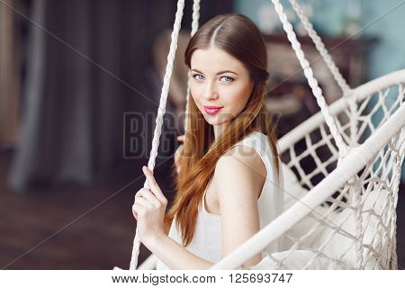 Beautiful Young Woman On A Swing Against Interior Studio Background