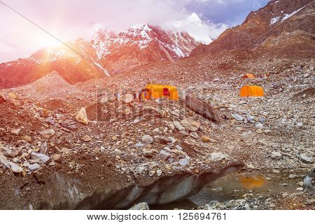 Mountain Expedition Camp on Glacier Moraine with Large Ice Crevasse and Melting Lake Foreground Clothing Hanged on Tent for Drying after Rain Sun Shining