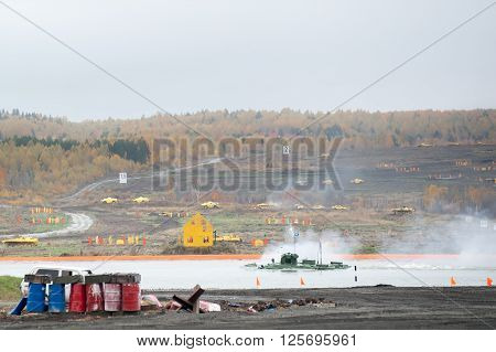 Nizhniy Tagil, Russia - September 27. 2013: BTR-82A armoured personnel carrier moves in water and shoots on shooting demonstration range. RAE-2013 exhibition