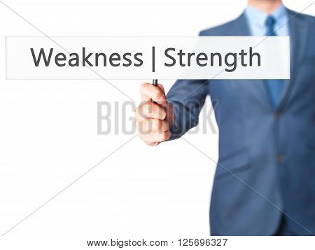 Weakness  Strength - Businessman Hand Holding Sign
