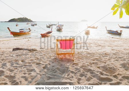 Beach chair on the sandy beach in front of the landscape of the ocean and island with traditional longtail boats in Lipe island Satun Thailand