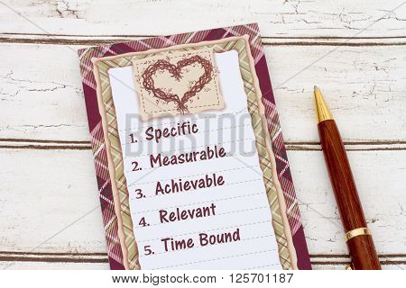 Writing your SMART Goals A notepad and pen on weathered wood background with text listing SMART Goals