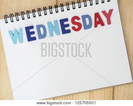 Wednesday word spell by wooden letters on blank notebook with wood background (Weekdays word series)