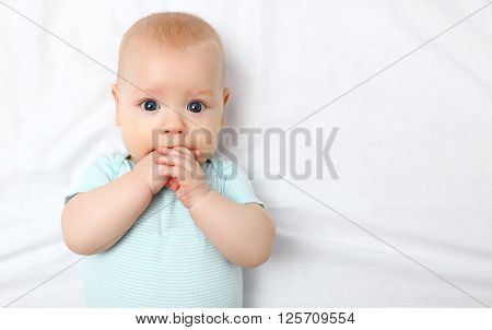 a happy newborn baby on the bed at home