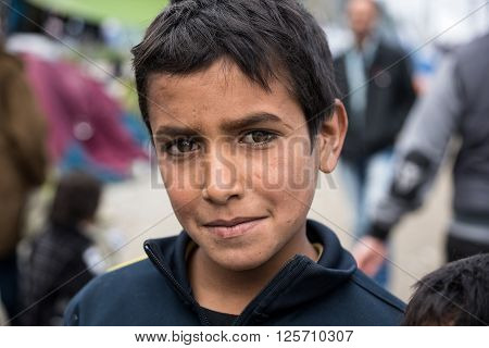 EIDOMENI, GREECE - MARCH 17, 2015: A boy from Syria poses near his tent on March 17, 2015 in the refugee camp of Eidomeni, Greece. For several weeks more than 10.000 refugees and immigrants wait here for the borders to open.