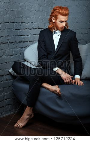 Red-haired man in a business suit sitting on the couch he is metrosexual.