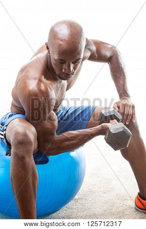 Toned lean muscle fitness man lifting weights on an exercise ball. Shallow depth of field.
