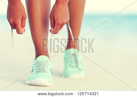 Healthy runner woman tying running shoes laces getting ready for beach jogging. Closeup of hands lacing cross training sneakers trainers for cardio workout. Female athlete living a fit and active life