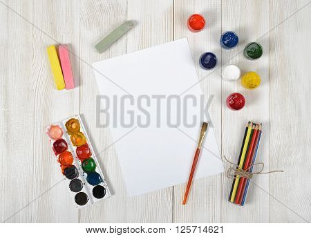 Work place of designer with colored pencils, brush, gouache jars, watercolor paints, colored chalks and a white paper in top view. Art disposition on wooden surface.