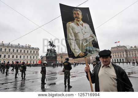 ST. PETERSBURG RUSSIA - MAY 1: Man with portrait of Soviet dictator Josef Stalin takes part in the May day demonstration in May 1, 2010