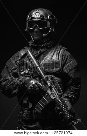 Spec ops police officer SWAT in black uniform and face mask studio shot