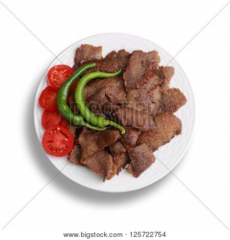 Traditional turkish doner kebab served on white plate with vegetable.