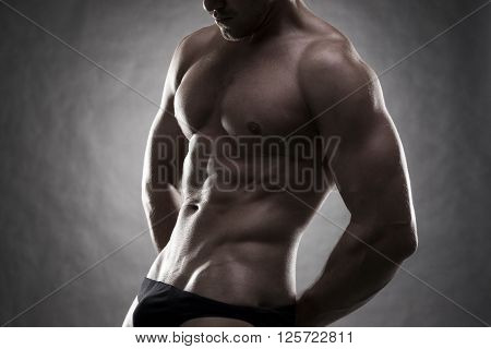 Handsome muscular bodybuilder posing on gray background. Low key close up studio shot . Sexy male body