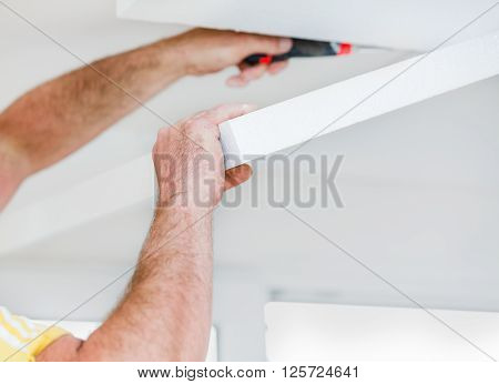 Handyman applying polyethylene foam panels to the ceiling. poster