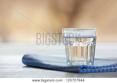 Glass of water with napkin  on light background