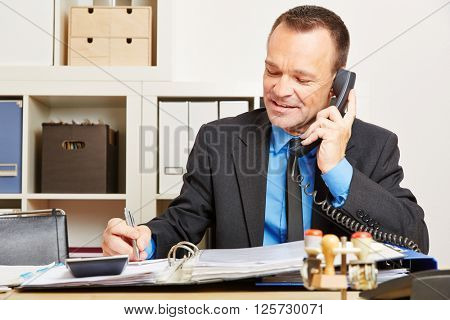 Business man talking to a customer support hotline on the phone in his office