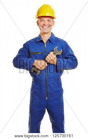 Smiling construction worker in boiler suit with safety helmet and jaw wrench