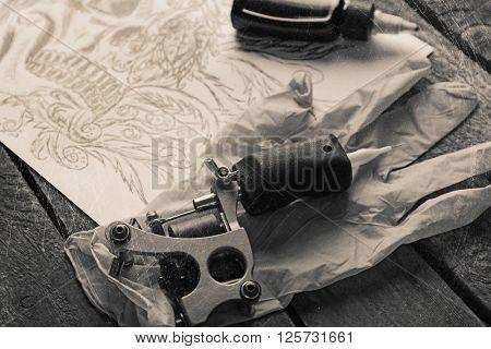 Tattoo machine and tattoo supplies on dark background. Retro stylization