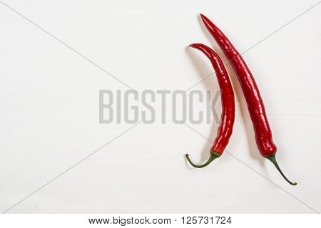 Two red hot chili peppers on a white background top view