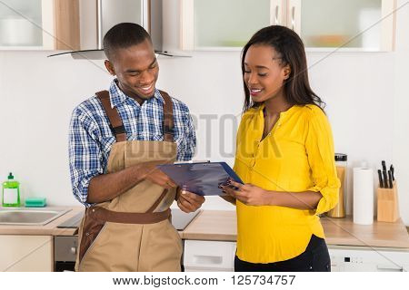 Handyman And Woman Looking At Clipboard