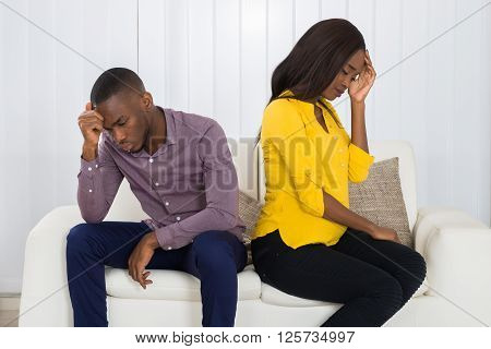 Couple Sitting Back To Back On Sofa
