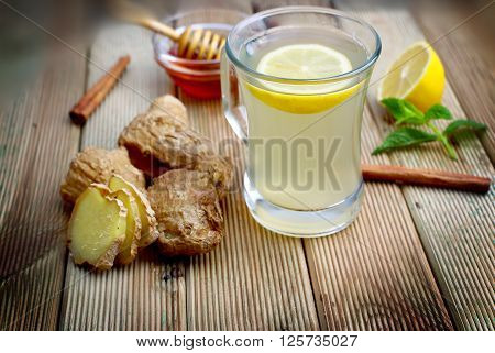 Ginger lemon honey mint leaves on wood background. A cup of ginger tea